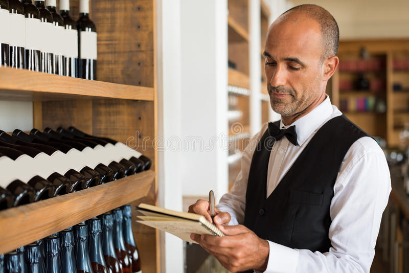 Sommelier writing inventory. For red wine in stock in a shop. Multiethnic man taking notes in winery with wine bottles stacked in rows on the shelves. Bartender stock images