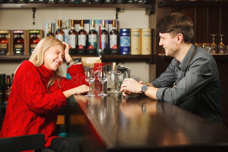 Sommelier y mujer que llevan el ron degustating del suéter rojo fotos de archivo