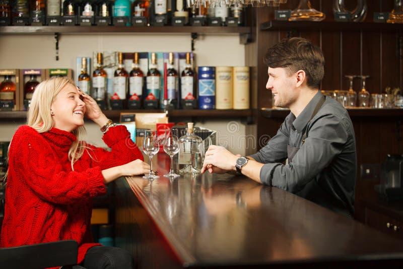 Sommelier y mujer que llevan el ron degustating del suéter rojo fotos de archivo libres de regalías