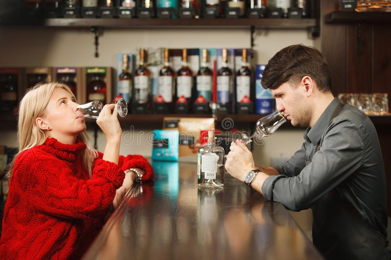 Sommelier and young woman tasting rum in restorant stock photos