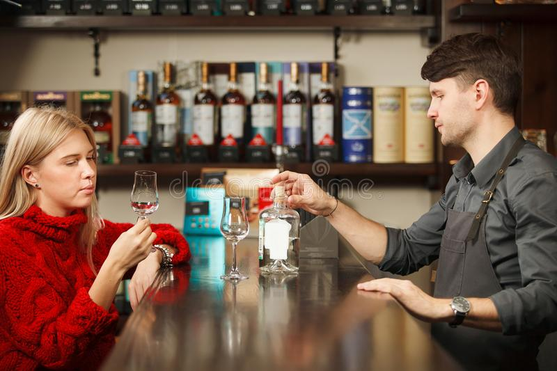 Sommelier and young woman tasting rum in restorant royalty free stock photos