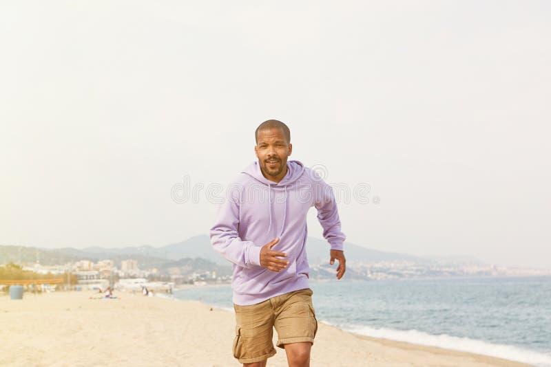 Sommer Active trägt Konzept zur Schau Attraktiver glücklicher junger afro-amerikanischer Mannhippie im Sportkapuzenpulli, der auf stockfoto