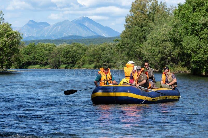 Sommer, der auf Halbinsel Kamtschatka - Gruppe Touristen schwimmen auf ruhigen Fluss auf Floss flößt stockfotografie