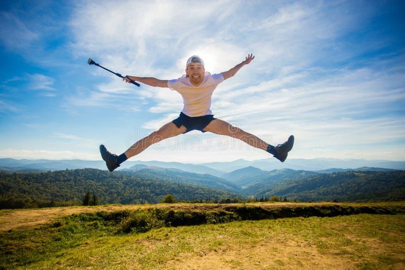 Sommer, der in den Bergen wandert Junger touristischer Mann in der Kappe mit den Händen oben auf Berge bewundert Natur stockbild