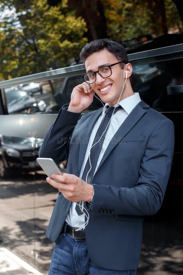 Sommer dreems Geschäftsmann in den Brillen, welche die Kopfhörer sich lehnen auf Wand auf dem hörenden Liedgrasen der Stadtstraße lizenzfreies stockfoto