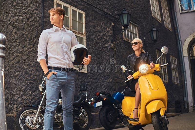 Sommer-Europa-Ferien, Datum, Romanze Attraktive Paare - reizend Blondine, die das schwarze Kleid sitzt auf einem Gelb tragen lizenzfreies stockfoto