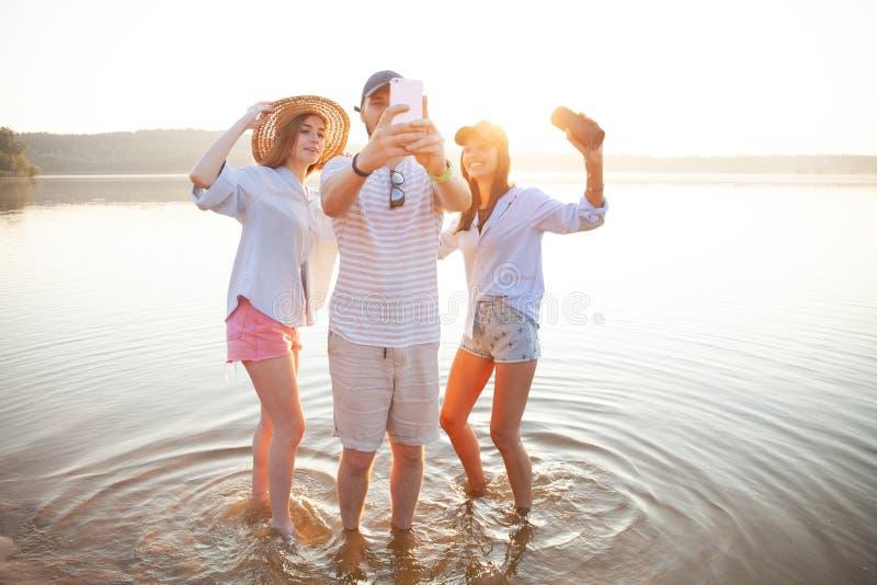 Sommer, Feiertage, Ferien und Glückkonzept - Gruppe Freunde, die selfie mit Smartphone nehmen lizenzfreie stockbilder