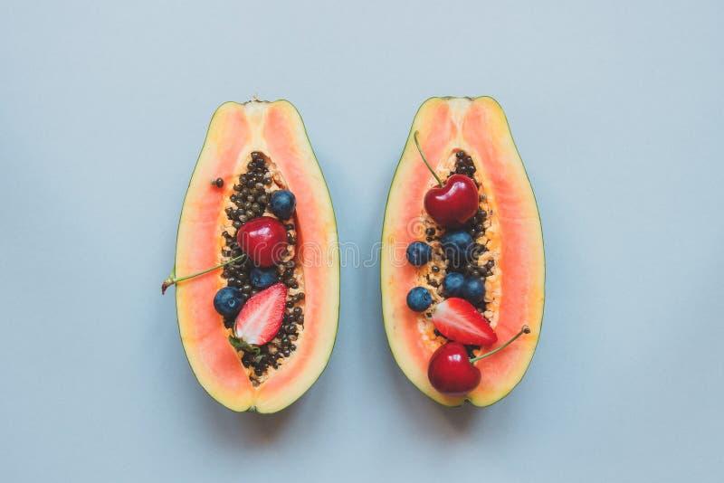 Sommer-Früchte Frische saftige Beeren und Papaya auf dem blauen Hintergrund, Draufsicht stockfotografie