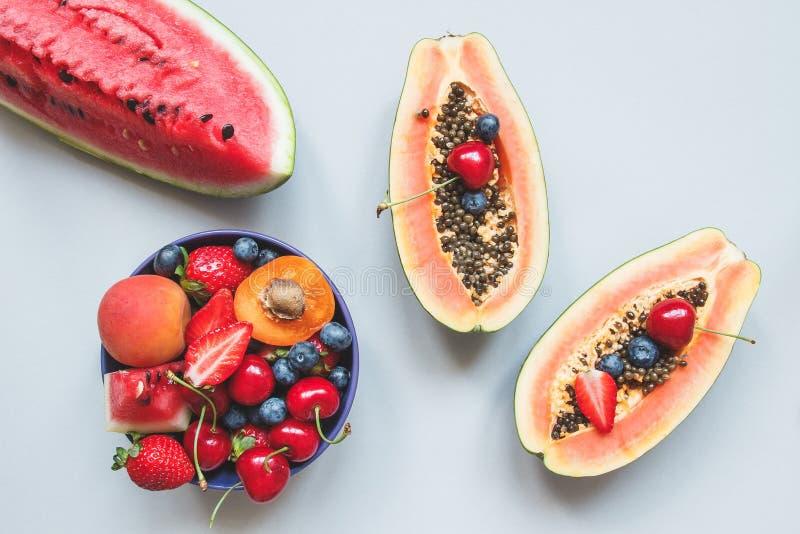 Sommer-Früchte Frische saftige Beeren, Wassermelone und Papaya auf dem blauen Hintergrund, Draufsicht stockfotos