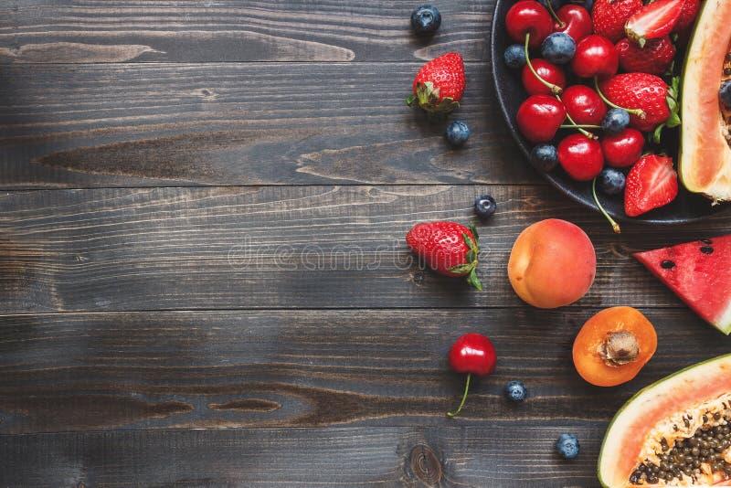 Sommer-Früchte Frische saftige Beeren, Wassermelone und Papaya auf dem schwarzen Holztisch, Draufsicht lizenzfreie stockbilder