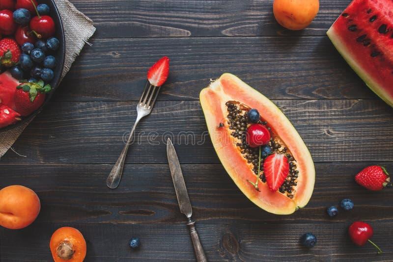 Sommer-Früchte Frische saftige Beeren, Wassermelone und Papaya auf dem schwarzen Holztisch, Draufsicht lizenzfreie stockfotografie