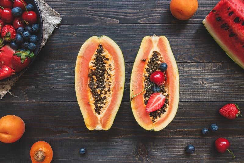 Sommer-Früchte Frische saftige Beeren, Wassermelone und Papaya auf dem schwarzen Holztisch, Draufsicht stockbilder
