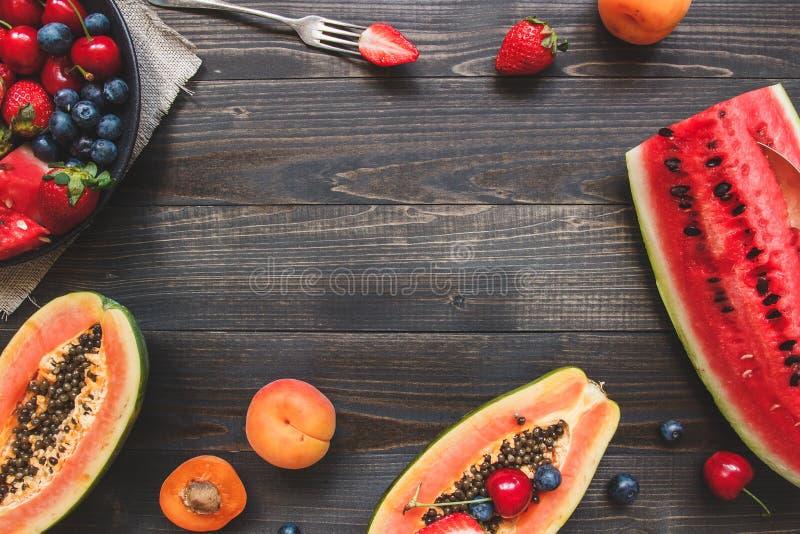 Sommer-Früchte Frische saftige Beeren, Wassermelone und Papaya auf dem schwarzen Holztisch, Draufsicht stockfoto