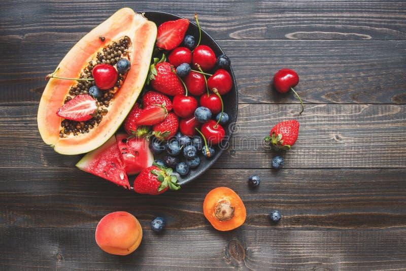 Sommer-Früchte Frische saftige Beeren, Wassermelone und Papaya auf dem schwarzen Holztisch, Draufsicht lizenzfreie stockfotos