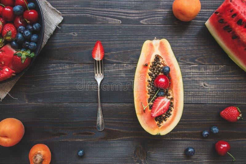 Sommer-Früchte Frische saftige Beeren, Wassermelone und Papaya auf dem schwarzen Holztisch, Draufsicht stockfotografie