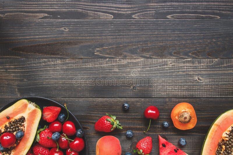 Sommer-Früchte Frische saftige Beeren, Wassermelone und Papaya auf dem schwarzen Holztisch, Draufsicht stockfotos