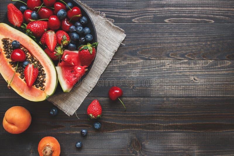 Sommer-Früchte Frische saftige Beeren, Wassermelone und Papaya auf dem schwarzen Holztisch, Draufsicht lizenzfreies stockbild