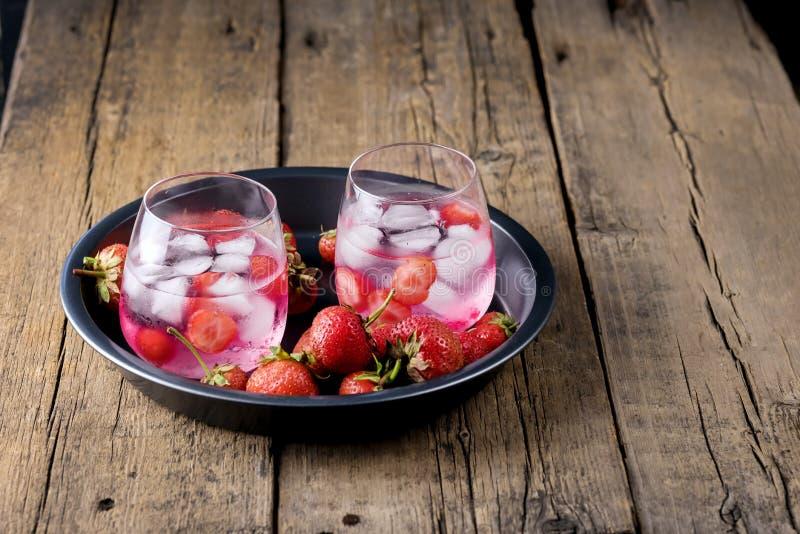 Sommer-frische gewürzte hineingegossene Wasser-Erdbeeredetox-Wasser-gesunde Diät-Getränk-Eiswürfel frische Erdbeere auf dem Schwa stockbilder