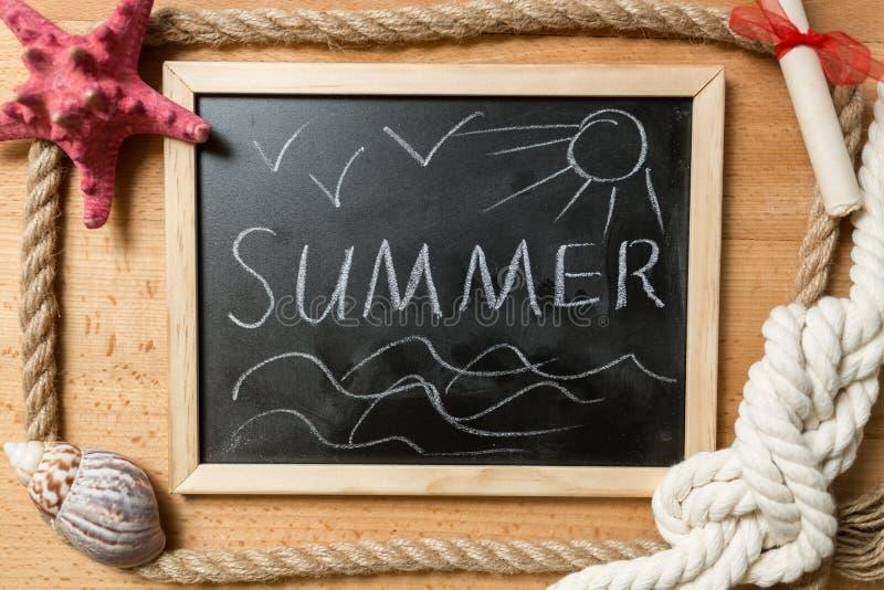 Sommer geschrieben auf Tafel mit Rahmen von Seilen, von Muscheln und von Knoten lizenzfreie stockfotografie