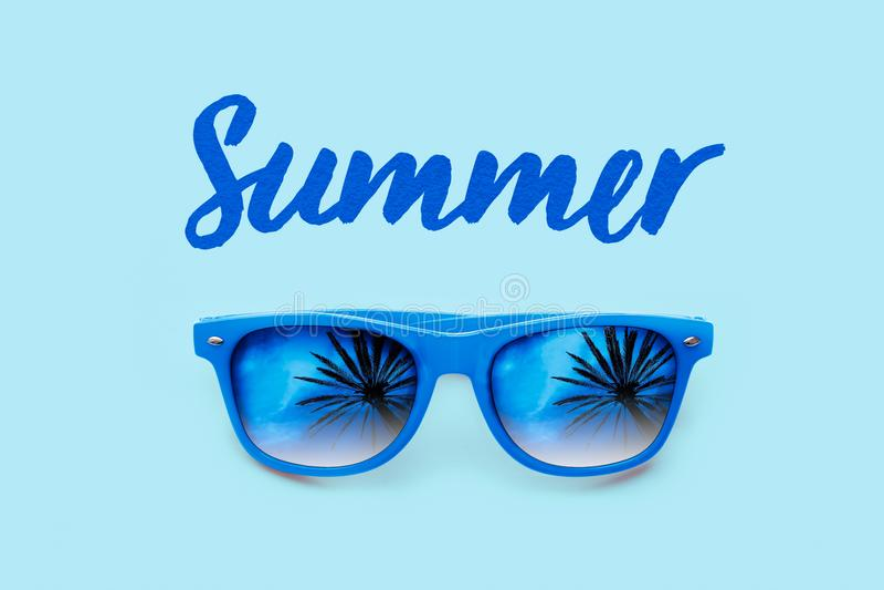 Sommer maserte blauen Text und blaue die Sonnenbrille mit Palmereflexionen lokalisiert in einem hellblauen Hintergrund stockfoto
