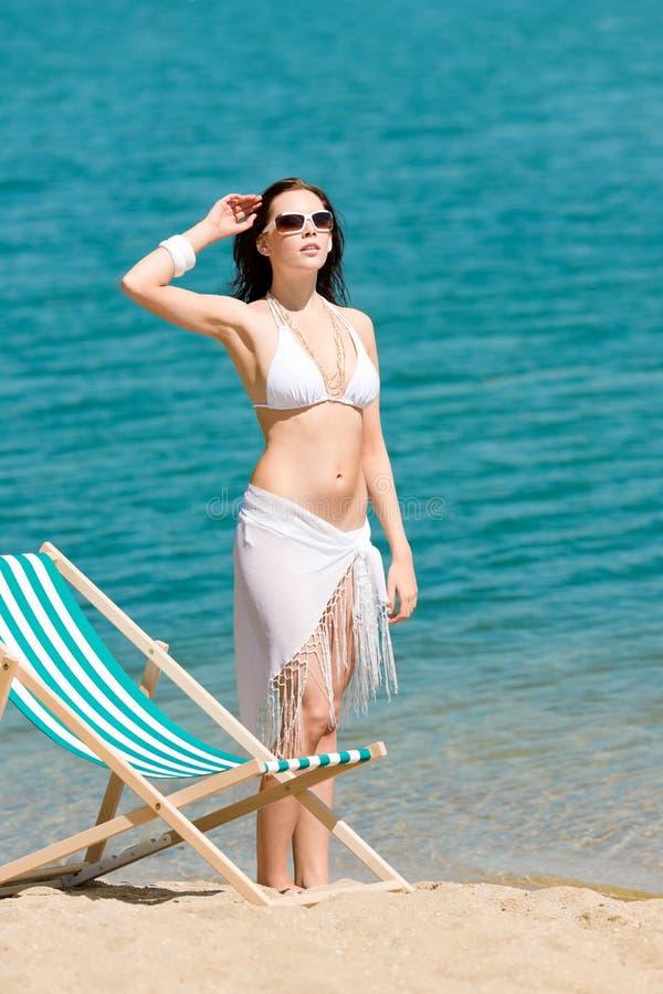 Sommer tonte die Frau, die auf Strand im Bikini ein Sonnenbad nimmt lizenzfreies stockfoto