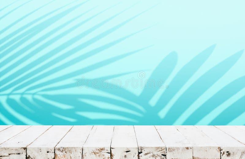 Sommer- und Naturproduktanzeige mit hölzernem Tabellenzähler auf Unschärfekokosnuss-Blatthintergrund in der blauen Farbe lizenzfreie stockfotos