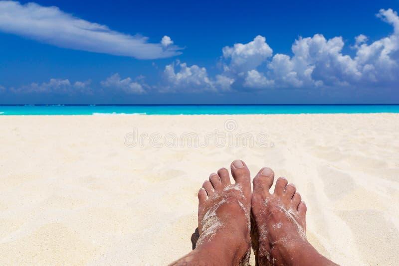 Sommer und Strandkonzept - Füße des Mannes auf tropischem Strand setzen auf den Strand stockbild