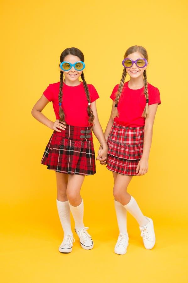 Sommer-Zusatz Ähnliche Ausstattungen der netten Schwestern der Mädchen bunte Sonnenbrille für Sommersaison tragen Sommermodetrend stockfoto