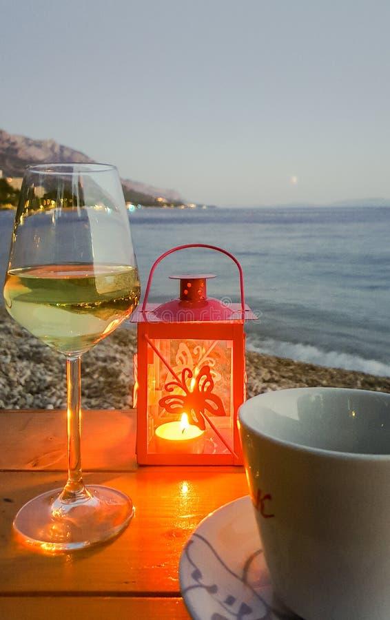Sommerabendlandschaft der Dolmatian-Küste durch ein Stillleben mit einem Glas des Weißweins, der Tasse Tee und des Kerzenständers stockbilder