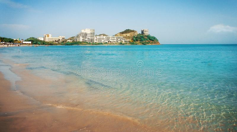 Sommerblauer Küstenstrand mit Gebäude und Vegetation auf dem Hintergrund lizenzfreie stockfotografie