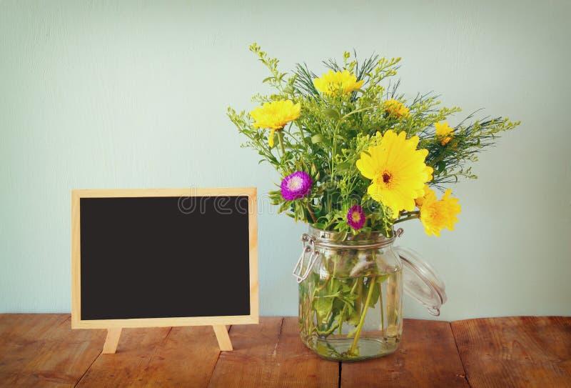 Sommerblumenstrauß von Blumen und von hölzerner Tafel auf dem Holztisch Kopieren Sie Platz lizenzfreie stockbilder