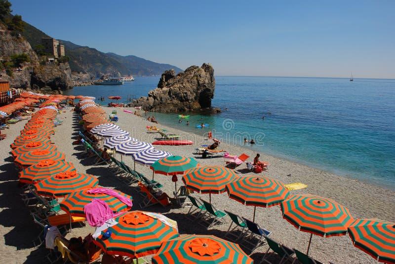 Sommerferien auf Italiener Riviera mit Leuchtorangegrünregenschirm stockfotografie