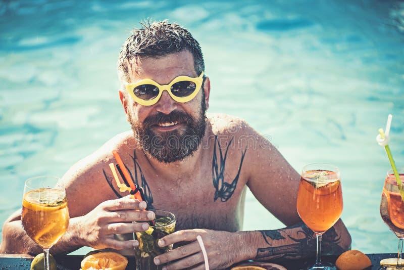 Sommerferien bei Miami Beach oder bei Malediven Pool-Party, Vitamin und N?hren Mannschwimmen und Getr?nkalkohol cocktail stockfotografie