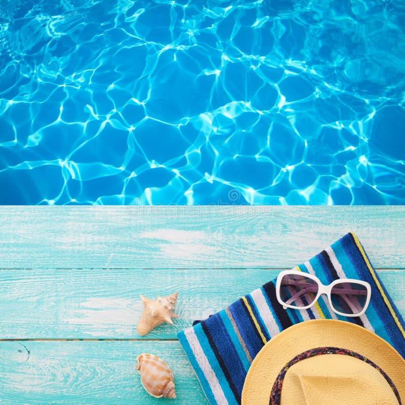 Sommerferien in der Strand-Küste Mode-Accessoire-Sommer-Flipflops, Hut, Sonnenbrille auf hellem Türkis verschalen nahe dem Pool stockfotos
