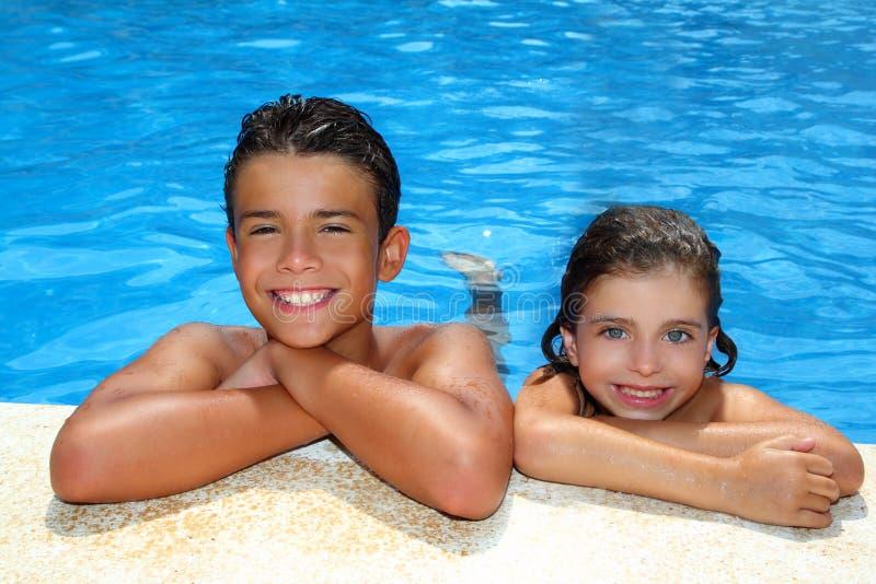 Sommerferien des Jungen und des kleinen Mädchens im Pool lizenzfreie stockfotos