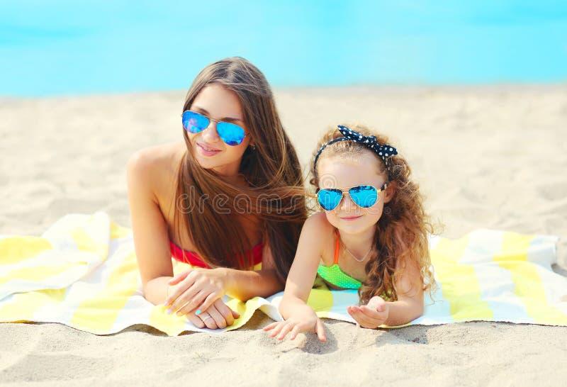 Sommerferien, Entspannung, Reise - Porträtmutter und Kind, das auf Strand liegt lizenzfreies stockfoto