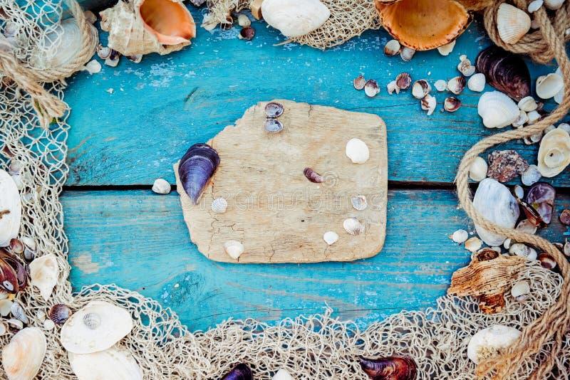 Sommerferien-Entspannungshintergrundthema mit Muscheln, Fischernetz, Hut, Seil, Steinen und verwittertem hölzernem blauem Hinterg lizenzfreie stockfotos