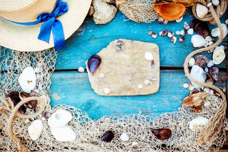 Sommerferien-Entspannungshintergrundthema mit Muscheln, Fischernetz, Hut, Seil, Steinen und verwittertem hölzernem blauem Hinterg stockbilder
