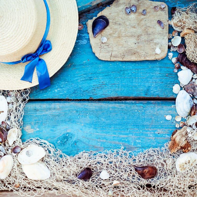 Sommerferien-Entspannungshintergrundthema mit Muscheln, Fischernetz, Hut, Seil, Steinen und verwittertem hölzernem blauem Hinterg stockfotografie