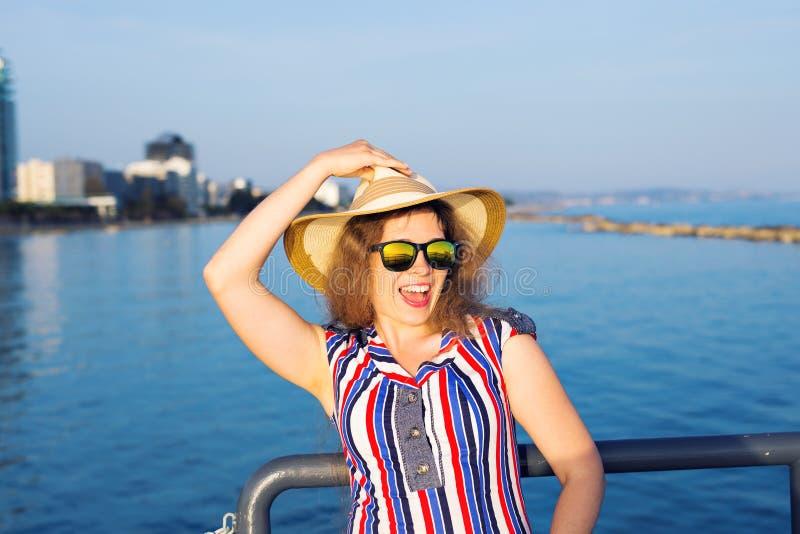 Sommerferien-, Ferien-, Reise- und Leutekonzept - lächelnde lachende tragende Sonnenbrille und Hut der jungen Frau auf Strand lizenzfreie stockbilder