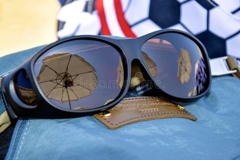 Sommerferien, Strandurlaub Reflexion von weißen Strandschirmen in der Sonnenbrille Sonnenbrille auf Hintergrund des Hutes stockbild