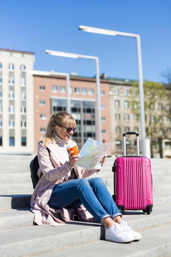 Sommerferien, Tourismus und Reisekonzept - junge Frau mit Karte und Koffer in der Stadt lizenzfreie stockbilder
