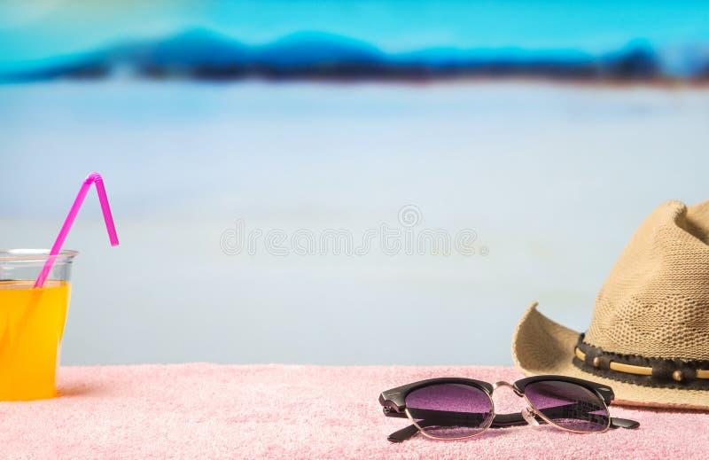 Sommerferienhintergrund mit freiem leerem leerem Kopienraum Geströmter Hut, Sonnenbrille und gelbes Getränk auf Tuch in der Parad lizenzfreies stockfoto