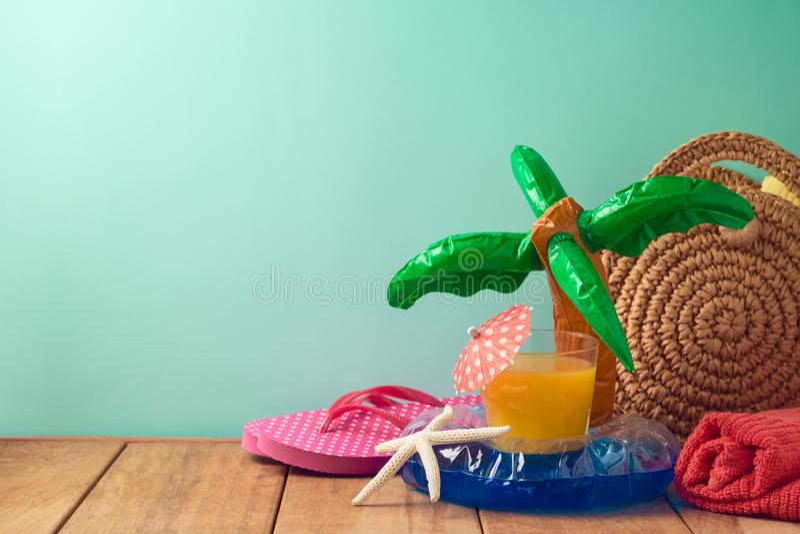 Sommerferienhintergrund mit Orangensaft, Strandeinzelteilen und Poolfloss auf Holztisch lizenzfreies stockfoto