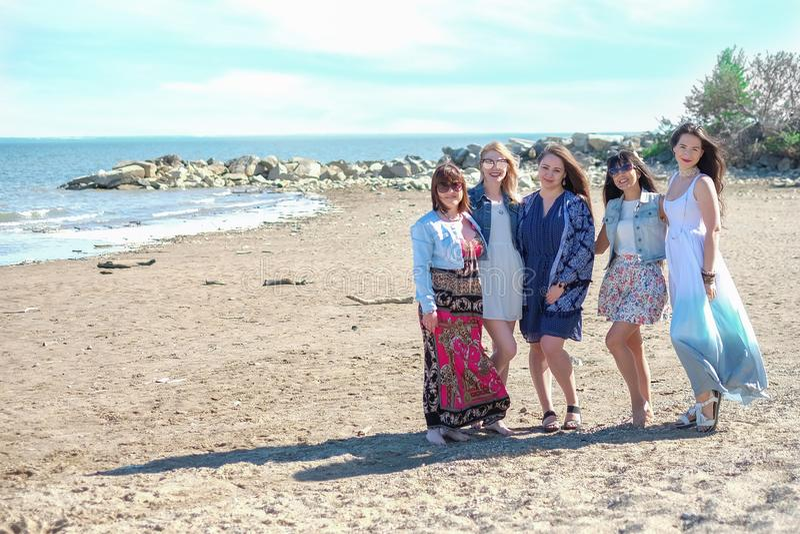 Sommerferienkonzept - Gruppe lächelnde junge Frauen steht auf der Küste still lizenzfreie stockfotografie