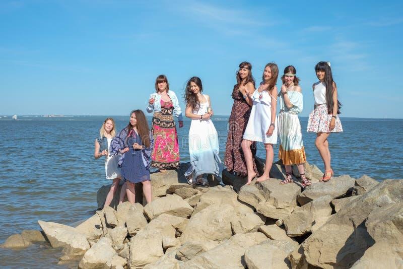 Sommerferienkonzept - Gruppe lächelnde junge Frauen steht auf der Küste still stockfotografie