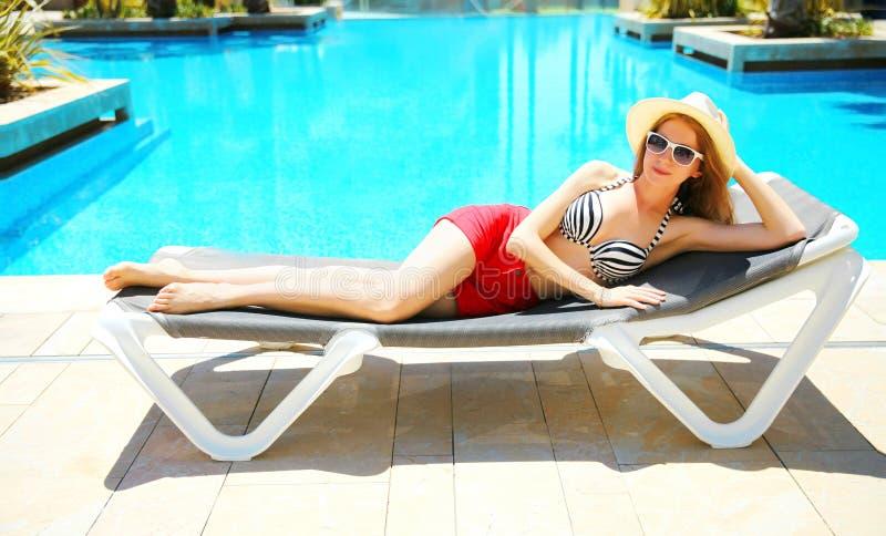 Sommerferienkonzept - hübsche Frau, die auf einem deckchair über einem Pool des blauen Wassers liegt lizenzfreie stockfotografie
