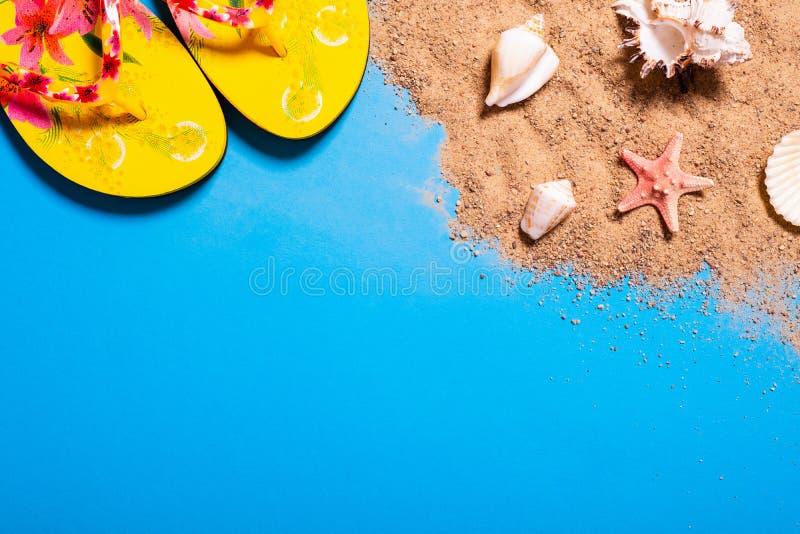Sommerferienkonzept mit Muschel-, Starfish- und Frauenstrandsandalen auf einem blauen Hintergrund und einem Sand stockfotos