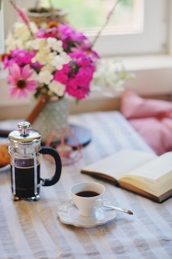 Sommerfrühstück im gemütlichen Landhaus Tabelle mit Blumenstrauß von Blumen von eigenem Garten, französische Presse mit Kaffee un lizenzfreie stockfotos
