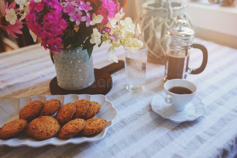 Sommerfrühstück im gemütlichen Landhaus Tabelle mit Blumenstrauß von Blumen von eigenem Garten, französische Presse mit Kaffee un lizenzfreie stockfotografie